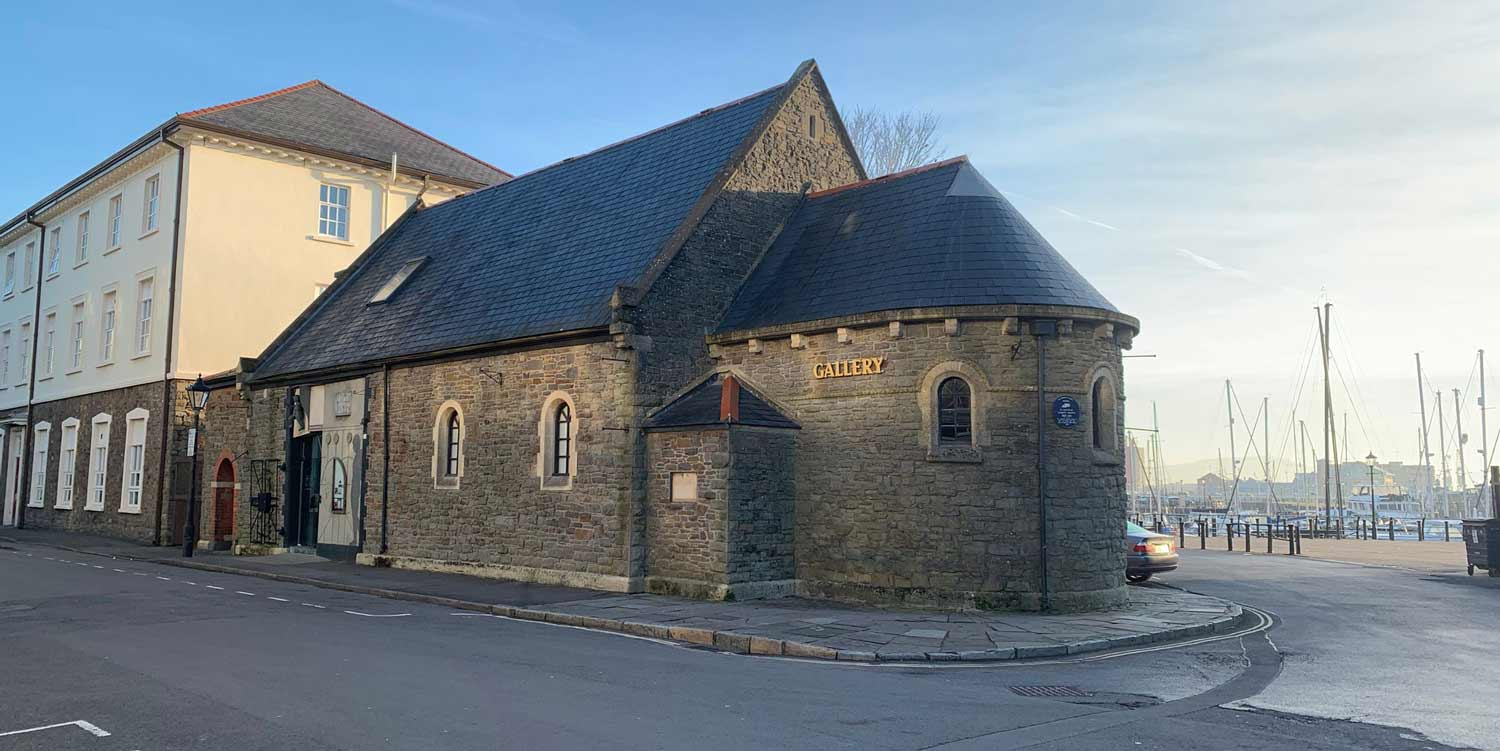 A photo of the outside of Mission Gallery on a sun day. A former seaman's mission - a type of church, with stone walls and slate roof.